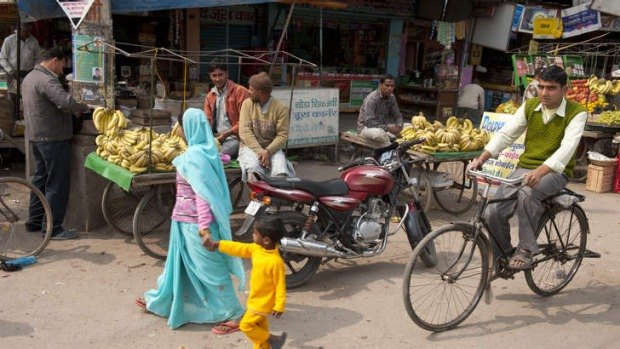 Pedestrians and a bicyclist pass fruit vendors on a New Delhi street.