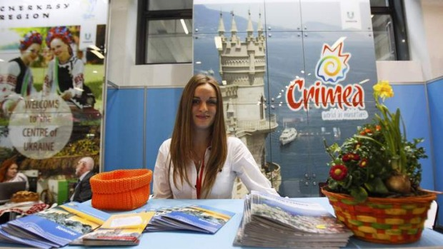 A volunteer waits for visitors at the booth representing Ukraine during the opening day at the International Tourism fair (ITB) in Berlin.