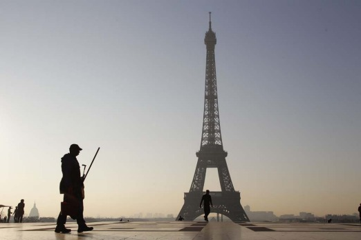A man walks at sunrise on the esplanade du Trocadero near the Eiffel tower.