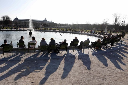 Shadows are cast as people relax in chairs around a fountain in the Tuileries Garden in central Paris.