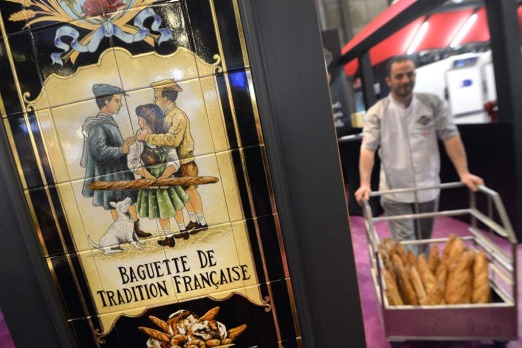 "A man carries a cart full of baguettes as a sign reads ""French traditionnal baguette"" during Europain 2014, a World ..."