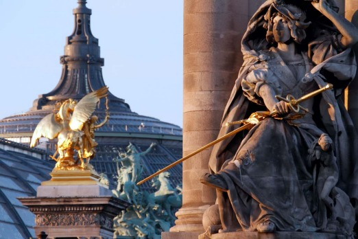 Sculptures and statues of the Alexandre III bridge with the Grand Palais in the background.