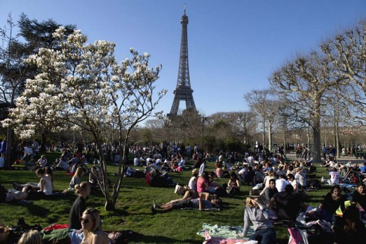 People enjoy the warm weather near the Eiffel Tower in Paris.