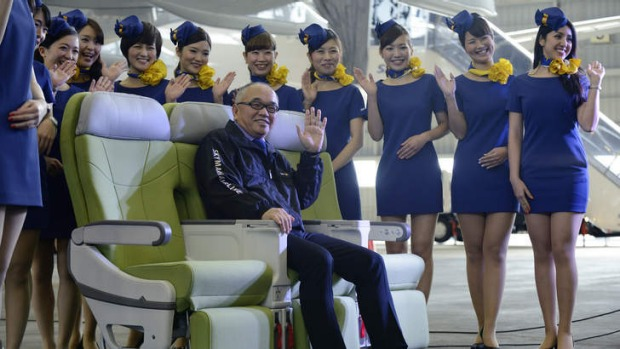 Shinichi Nishikubo, president of Skymark Airlines, poses for a photograph with members of the company's cabin crew.