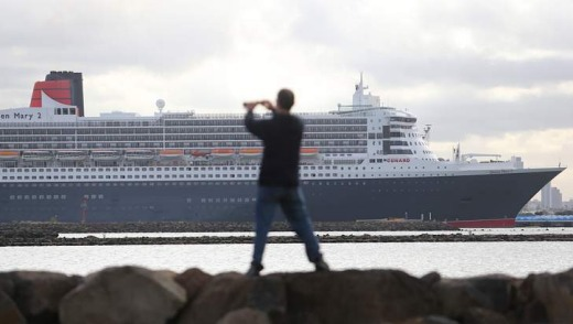 A passer-by takes a photo of Queen Mary 2 at Webb Dock.