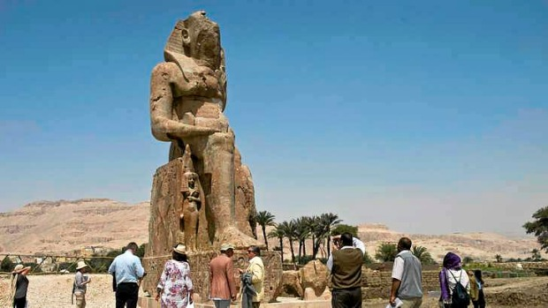 Tourists and journalists stand next to a newly displayed statue of pharaoh Amenhotep III and his wife Tiye (Down) in ...