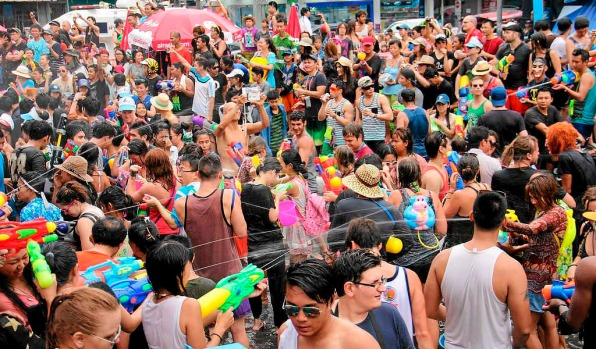 Local and tourists gather and use water guns to splash water to each other on the eve of Songkran festival or ancient ...