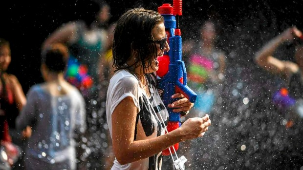 A reveller reacts as she participates in a water fight during Songkran Festival celebrations at Khaosan road in Bangkok. ...
