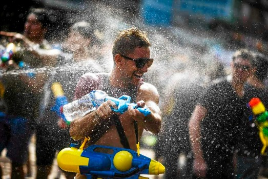 A reveller uses a water gun as she participates in a water fight during Songkran Festival celebrations at Khaosan road ...
