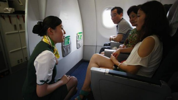 A crew member of Spring Airlines talks with travellers.