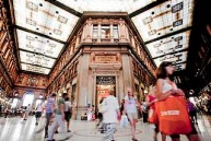 Pedestrians pass stores as they walk through the Alberto Sordi shopping mall in Rome, Italy, on Friday, Aug. 5, 2011. ...