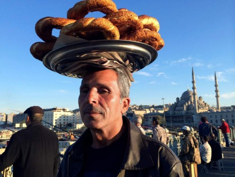 A man carrys food on the Galata bridge.