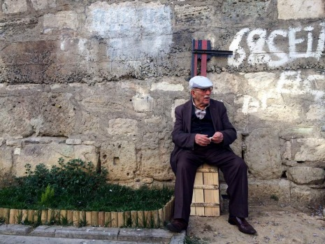 Sultanahmet. A man sits on a box and watches people pass by.