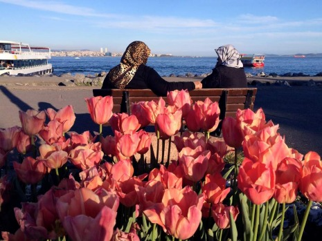 Cankurtaran. Two ladies enjoy the afternoon sun and the water view in front of tulips.