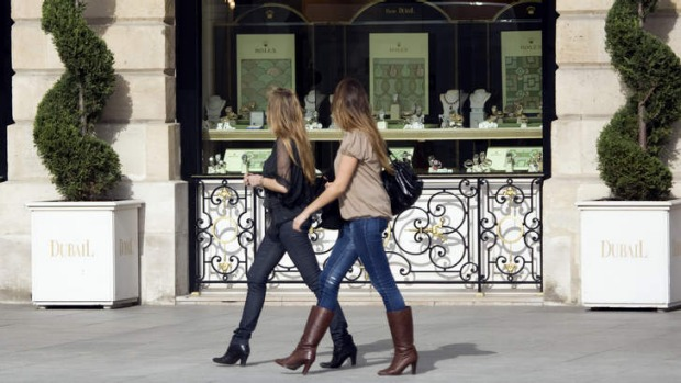 Women walk past a window display in Paris.