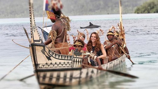 Duchess of Cambridge and Prince William are followed by locals dressed as 'sharks' as they travel in a traditional canoe ...