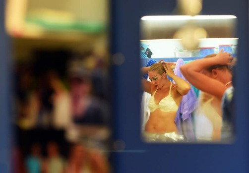 "A 'mermaid' is reflected on a mirror in her locker room as she prepares to perform an underwater show ""Little Mermaid"" ..."