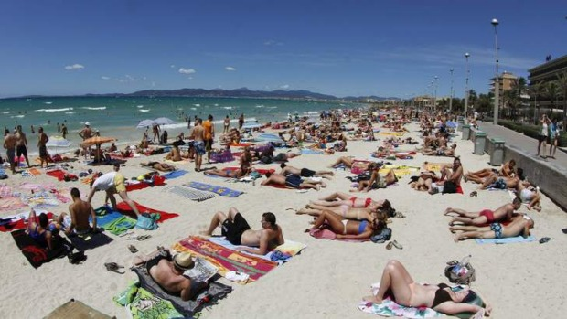 Tourists crowd Palma de Majorca's Arenal beach.