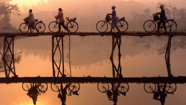 Indonesian villagers push their bicycles across a bamboo bridge as sun rises behind them outside Yogyakarta city in ...