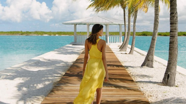 Young woman strolling on beach pier, Providenciales, Turks and Caicos Islands, Caribbean.