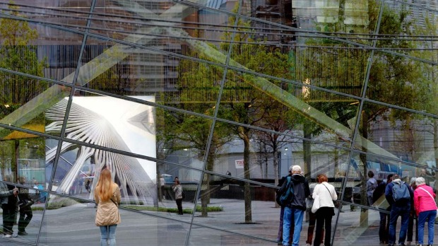 People peering through the windows of the National September 11 Memorial Museum.