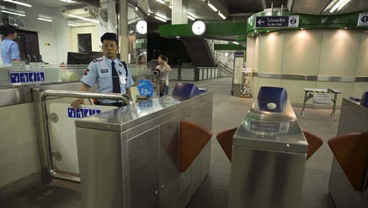 A Thai security guard stands at the entrance to the Bangkok Skytrain after it closed at 9pm stranding thousands of ...