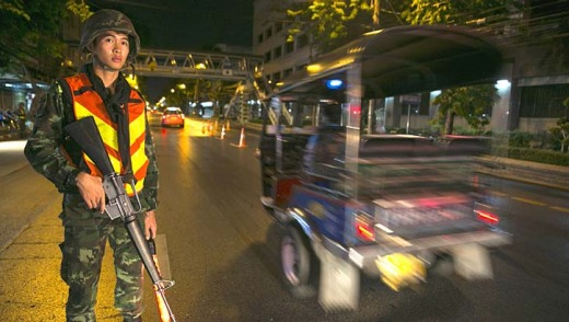 A Thai soldier stands guard at a checkpoint after a curfew started at 10pm in Bangkok, Thailand.