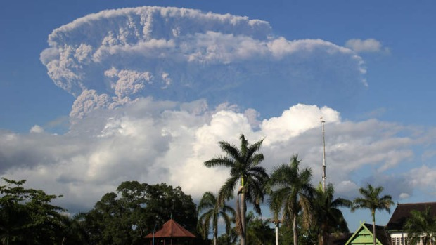 A giant cloud of ash and steam rise from erupting Sangeang Api volcano seen from Bima town on Sumbawa island.
