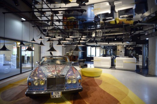 "A Rolls Royce car in a lobby of the ""Molitor"" luxury resort with hotel, spa, swimming pool and restaurant in Paris."