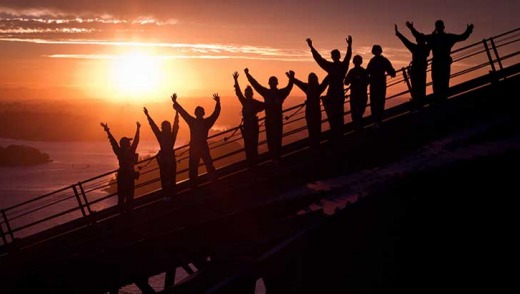 Climbers cheer their efforts at the top of the bridge at dawn.