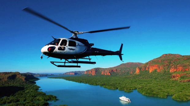 "Cruising the Kimberley Coast, in the far North-West of Australia, with the luxury cruise ship ""True North"". Its onboard helicopter allows guests to see the rugged terrain from the air and enjoy sweeping views of the gorges, mangroves and sandstone cliffs."