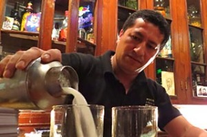 Bartender pouring a pisco sour.
