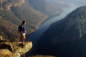 Person standing on edge of cliffs at God's Window overlooking Blyde River Canyon, South Africa.