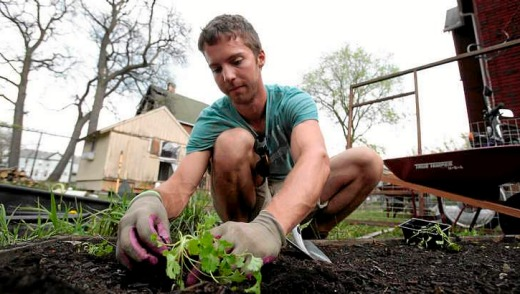 Darin McLeskey plants a vegetable garden in the back yard of one of the properties he purchased for bargain price and ...