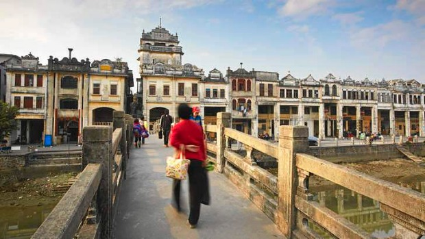 People crossing the bridge in front of colonial architecture, Chikanzhen, Guangdong.