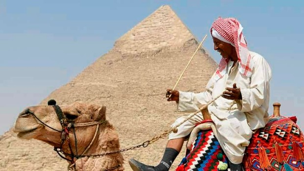 A guide waits for tourist to take them for a ride on his camel in front of the Great Pyramid of Giza.
