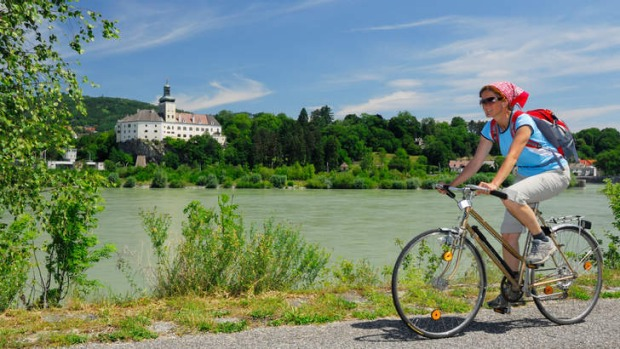 Saddle up: cycling along the Danube with Persenbeug Castle in the background.