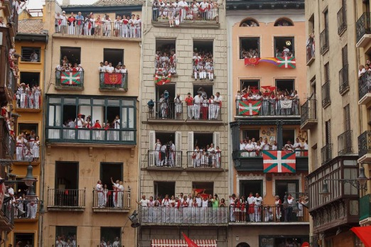 Revellers stand on balconies watching the opening and the firing of the 'Chupinazo' rocket which starts the 2014 ...