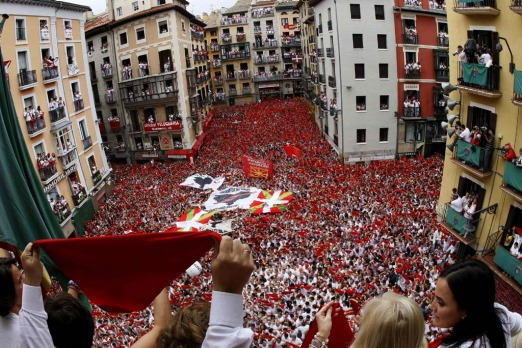 People cheer after hearing the midday Chupinazo rocket announcing the start of the San Fermin festival in Pamplona. Tens ...