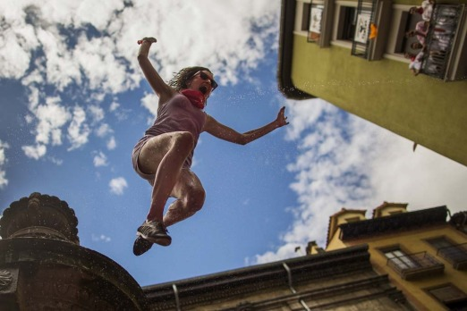 A reveller jumps from a fountain onto the crowd below, after the launch of the 'Chupinazo' rocket, to celebrate the ...