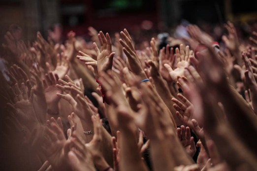 Revellers hold up their hands during the launch of the 'Chupinazo' rocket, to celebrate the official opening of the 2014 ...