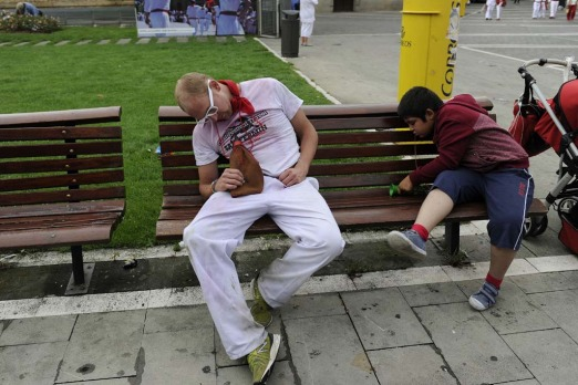 A reveller naps on a bench following the midday Chupinazo rocket announcing the start of the San Fermin festival in Pamplona.