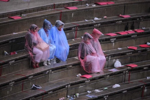 People shelter by the rain during a bullfight at San Fermin Fiestas, in Pamplona, Spain.
