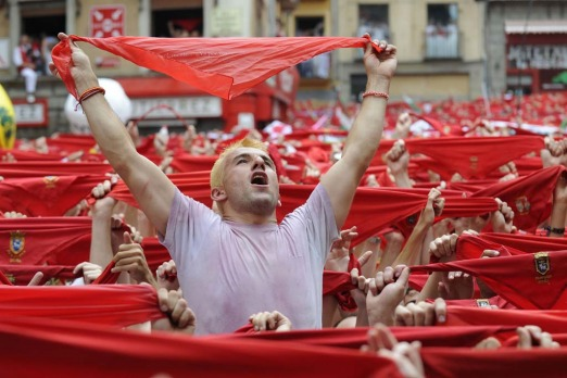 Participants hold red scarves as they celebrate the 'Chupinazo' to mark the start at noon sharp of the San Fermin ...