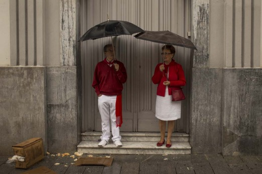Revelelrs dressed in traditional outfits cover themselves from the rain during the opening day of the 2014 San Fermin ...