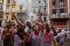 Revellers are soaked in water and wine thrown from balconies during the opening and the firing of the 'Chupinazo' rocket ...