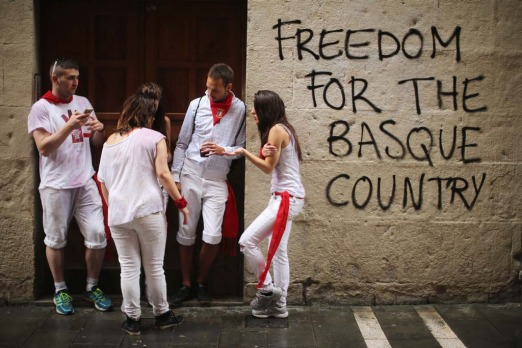 "Revellers shelter from the rain next to fresh graffiti saying ""Freedom For The Basque Country"" after the opening and the ..."