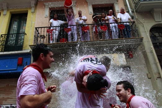 Revellers are drenched with water thrown from a balcony following the midday Chupinazo rocket announcing the start of ...