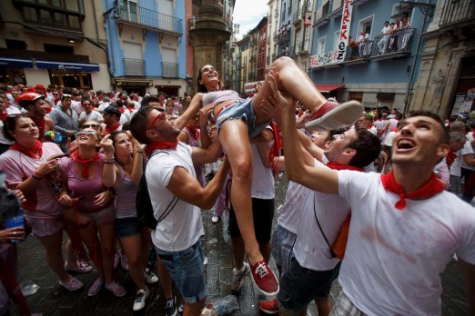Revellers throw a woman to the air during the opening and the firing of the 'Chupinazo' rocket which starts the 2014 ...