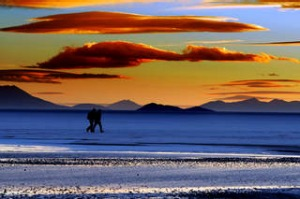 Two people walking across the Salar de Uyuni in Bolivia with fiery sunset  South America.